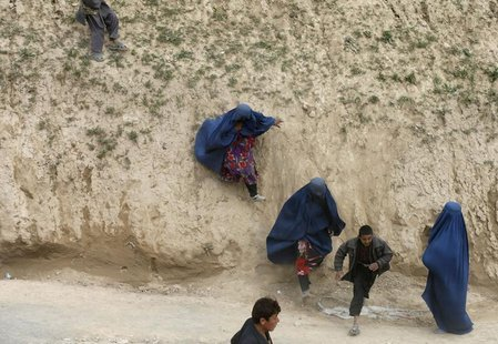 Afghan survivors arrive to receive aid near the site of a landslide at the Argo district in Badakhshan province May 4, 2014. REUTERS/Mohamma