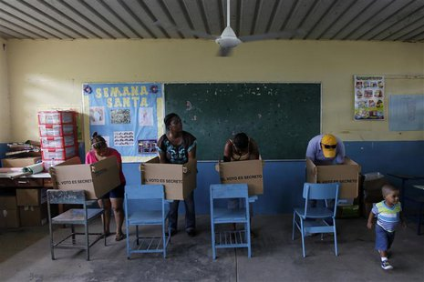 Residents prepare their ballots in voting booths during the presidential election at a polling station in Panama City May 4, 2014. REUTERS/
