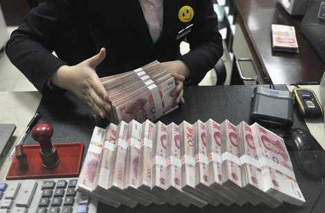A clerk arranges bundles of 100 Chinese yuan banknotes at a branch of China Merchants Bank in Hefei, Anhui province March 17, 2014. REUTERS/