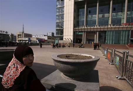 A Uighur woman looks back near exit of the South Railway Station, where three people were killed and 79 wounded in Wednesday's bomb and knif