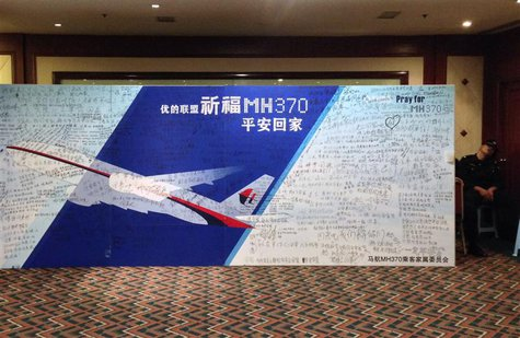 A policeman takes a nap beside a board written with messages for passengers onboard the missing Malaysia Airlines Flight MH370 during a clos