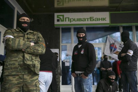 Masked pro-Russian activists stand outside a branch of Ukraine's Privatbank during a protest in Donetsk, eastern Ukraine April 28, 2014. REU