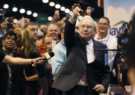 Berkshire Hathaway CEO Warren Buffett points after throwing a newspaper during a competition at a trade show, at the company's annual meetin