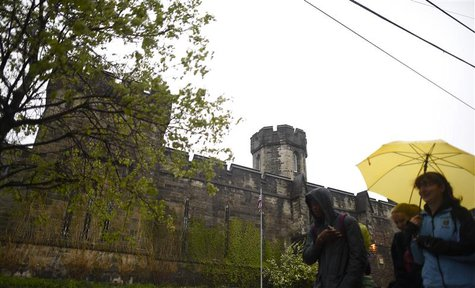 Pedestrians pass in front of the now-closed Eastern State Penitentiary in Philadelphia, Pennsylvania April 30, 2014. REUTERS/Mark Makela