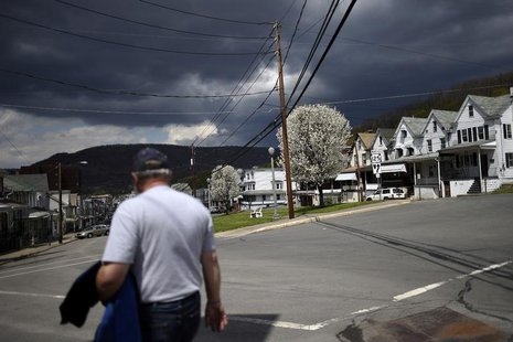 A man walks down Market Street with darkening clouds forming above the bluff in the distance in Shamokin May 1, 2014. REUTERS/Mark Makela