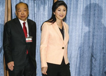 Thailand's Prime Minister Yingluck Shinawatra (R) and Deputy Prime Minister Surapong Tovichakchaikul arrive before a meeting with the Electi