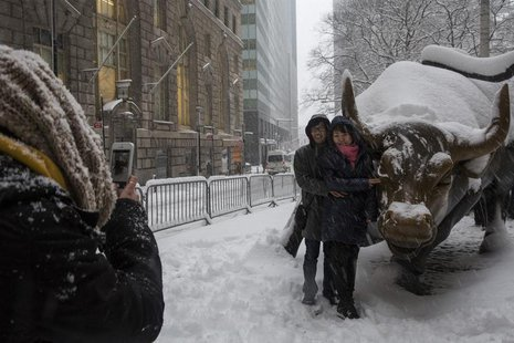 Tourists pose for a photo with the Charging Bull during a morning snow in New York's financial district near Wall Street February 13, 2014.