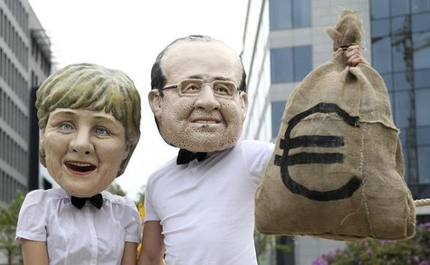 Activists wearing masks depicting German Chancellor Angela Merkel (L) and French President Francois Hollande stage a protest outside a meeti