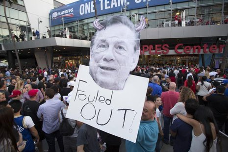 A supporter holds a photo cutout of Los Angeles Clippers owner Donald Sterling while standing in line for the NBA Playoff game 5 between Gol