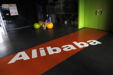 An employee sits next to a logo of Alibaba during a media tour organised by government officials at the company's headquarters on the outski