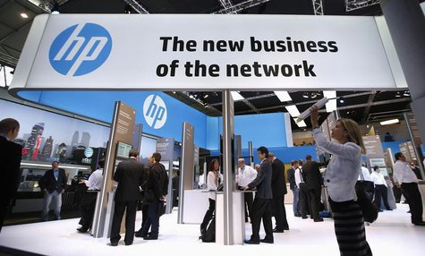 A visitor takes a photo with a tablet in front of a Hewlett-Packard (HP) stand at the Mobile World Congress in Barcelona, February 27, 2014.