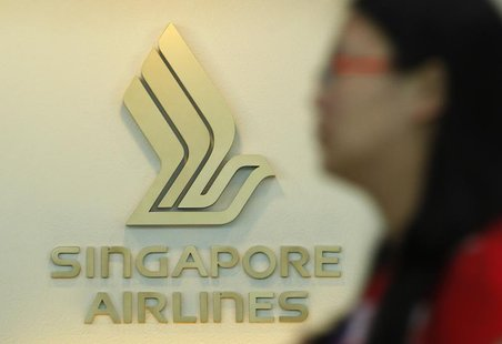 A woman walks past a Singapore Airlines (SIA) logo at a ticketing booth at Changi airport in Singapore May 14, 2013. REUTERS/Edgar Su