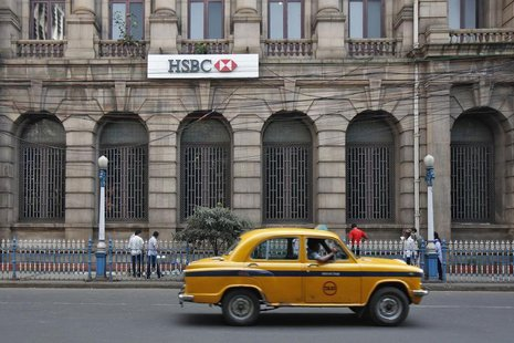 A yellow ambassador taxi drives past the HSBC bank building in Kolkata November 5, 2013. REUTERS/Rupak De Chowdhuri