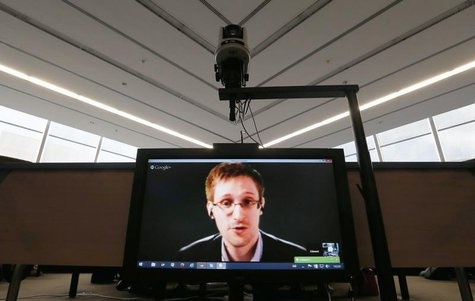 Accused government whistleblower Edward Snowden is seen on a screen as he speaks via video conference with members of the Committee on legal
