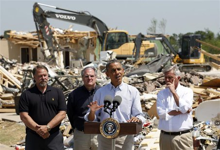 Amid the wreckage, U.S. President Barack Obama speaks as he visits the tornado devastated town of Vilonia, Arkansas May 7, 2014. With Obama