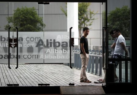 Employees stand next to a glass door with logos of Alibaba during a media tour organised by government officials at the company's headquarte