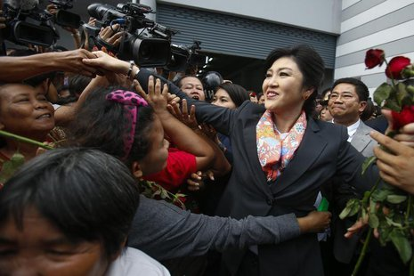 Thailand's Prime Minister Yingluck Shinawatra greets her supporters as she leaves the Permanent Secretary of Defence office in Bangkok May 7