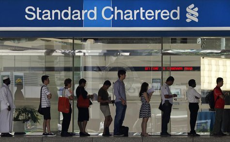People queue up outside a Standard Chartered Bank branch before operation hours at the central business district in Singapore January 23, 20