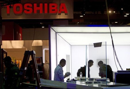 Technicians with TCL Communication put together a display near the Toshiba booth in preparation for the 2014 Consumer Electronics Show (CES)