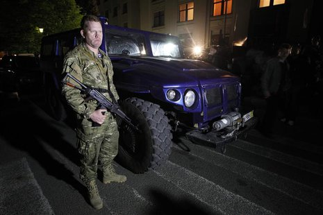 "An armed pro-Russian activist stands beside a ""Tigr"" light armoured vehicle, which was a donation from the Liberal Democratic Party of Russi"