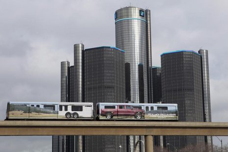 Two cars of the 'people mover' public rail are seen covered with a advertisement for the 2014 Chevy Silverado pickup truck as they move past