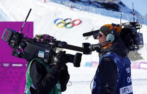 Media cameramen shouldering video cameras chat during the women's snowboard slopestyle qualifying round at the 2014 Sochi Olympic Games in Rosa Khutor February 6, 2014. CREDIT: REUTERS/MIKE BLAKE