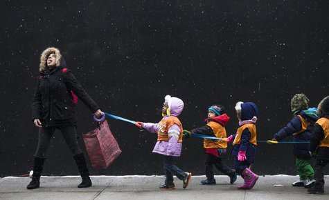 A schoolteacher, attempts to catch snowflakes while leading her students to a library from school in the Harlem neighborhood, located in the