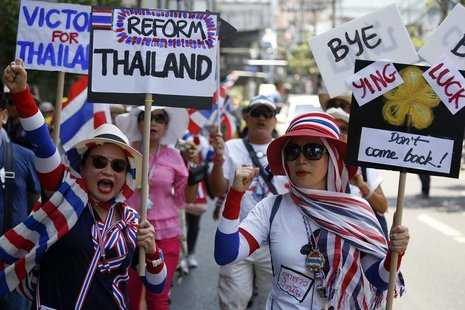 Anti-government protesters carry signs against ousted Prime Minister Yingluck Shinawatra as they march in central Bangkok May 8, 2014. REUTE