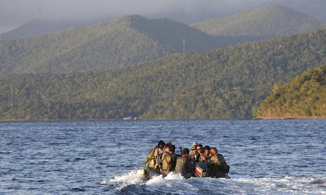 Members of the Philippine marines are transported on a rubber boat from a patrol ship after conducting a mission on the disputed Second Thom