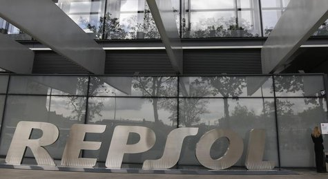 A woman stands beside the logo of Spanish oil company Repsol outside its headquarters in Madrid May 16, 2013. REUTERS/Sergio Perez