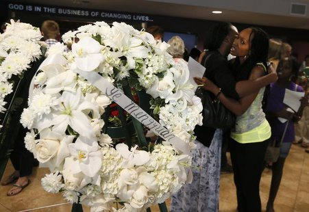 Women embrace near wreaths after a prayer vigil for the victims 0f the Asiana Airlines crash at West Valley Christian School in West Hills,