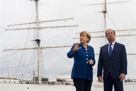 German Chancellor Angela Merkel (L) and French President Francois Hollande pose for pictures in front of the tall ship Gorch Fock I, in the