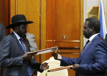 South Sudan's rebel leader Riek Machar (R) and South Sudan's President Salva Kiir (L) exchange signed peace agreement documents in Addis Aba