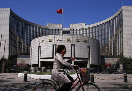 A woman rides past the headquarters of the People's Bank of China, the Chinese central bank, in Beijing, April 3, 2014. REUTERS/Petar Kujund