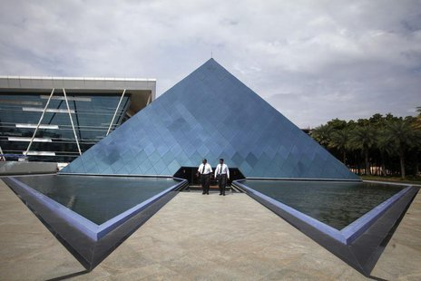 Employees walk in front of a pyramid-shaped building at the Infosys campus in the Electronic City area of Bangalore September 4, 2012. REUTE