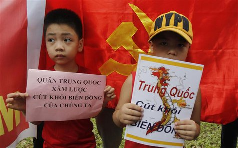 "Boys hold placards which read ""Chinese invaders, get out of the East Sea (South China Sea)"" (L) and ""China get out, East Sea"", in front of t"
