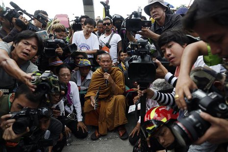 Thai Buddhist monk and protest leader Luang Pu Buddha Issara (C) is surrounded by his supporters and reporters as anti-government protesters