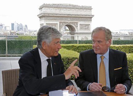 Maurice Levy (L), French advertising group Publicis Chief executive, and John Wren, head of Omnicom Group, gesture during a joint signature