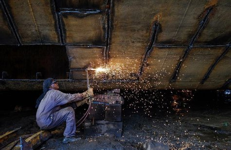 A worker repairs a vessel at a ship repair yard in Mumbai May 2, 2014. REUTERS/Danish Siddiqui