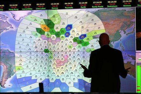 A member of staff at satellite communications company Inmarsat works in front of a screen showing subscribers using their service throughout