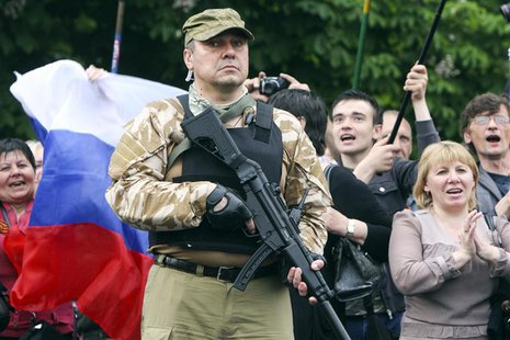 A bodyguard hold his weapon during a rally to mark and celebrate the announcement of the results of the referendum on the status of Luhansk
