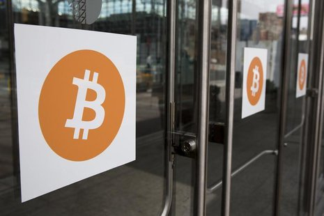 Bitcoin themed stickers stand attached to glass doors during the Inside Bitcoins: The Future of Virtual Currency Conference in New York Apri