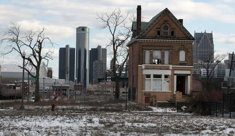 A vacant, boarded up house is seen in the once thriving Brush Park neighborhood with the downtown Detroit skyline behind it in Detroit, Mich
