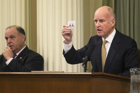 California Governor Jerry Brown holds a playing card detailing the state's fluctuating budgets during his State of the State address at the