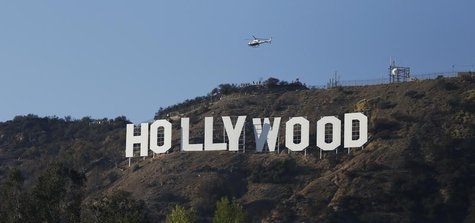 A Los Angeles Police Department (LAPD) helicopter flies over the Hollywood sign in Hollywood, California February 21, 2014. REUTERS/Mario An