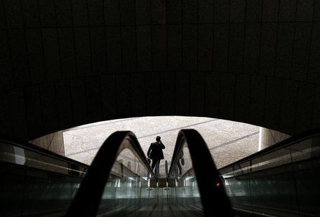 An office worker uses his mobile phone as he leaves an office building in central Sydney July 30, 2013. REUTERS/Daniel Munoz