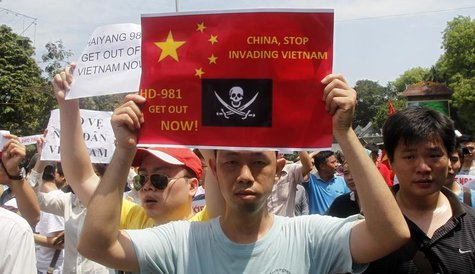 Protesters hold anti-China placards while marching in an anti-China protest on a street in Hanoi May 11, 2014. REUTERS/Kham