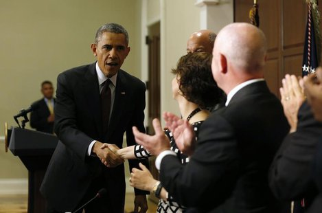 U.S. President Barack Obama (L) shakes hands with Director of Domestic Policy Cecilia Munoz after speaking to law enforcement leaders from a