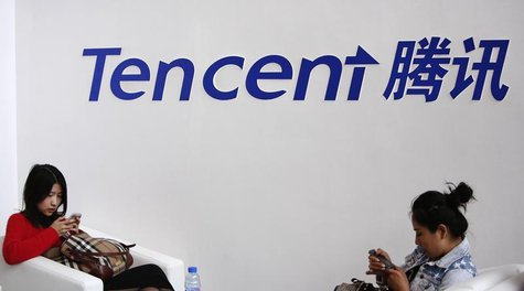 Visitors use their smarts phones underneath the logo of Tencent at the Global Mobile Internet Conference in Beijing May 6, 2014. REUTERS/Kim