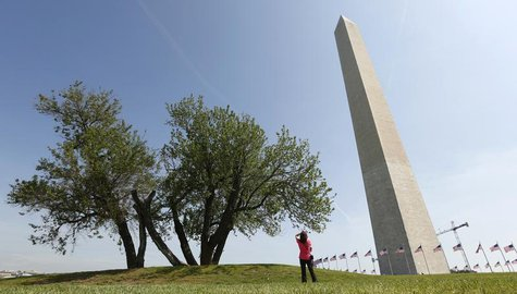 A woman stops to photograph the re-opened Washington Monument in Washington May 12, 2014. REUTERS/Kevin Lamarque